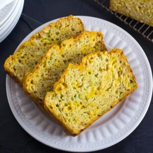 3 thick slices of cheesy beer bread arranged on a decorative white plate resting on a dark surface; cooling rack in background