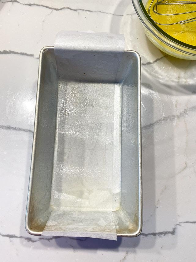 9 inch or 23 cm loaf pan prepped with nonstick spray and lined with parchment paper on white marble surface