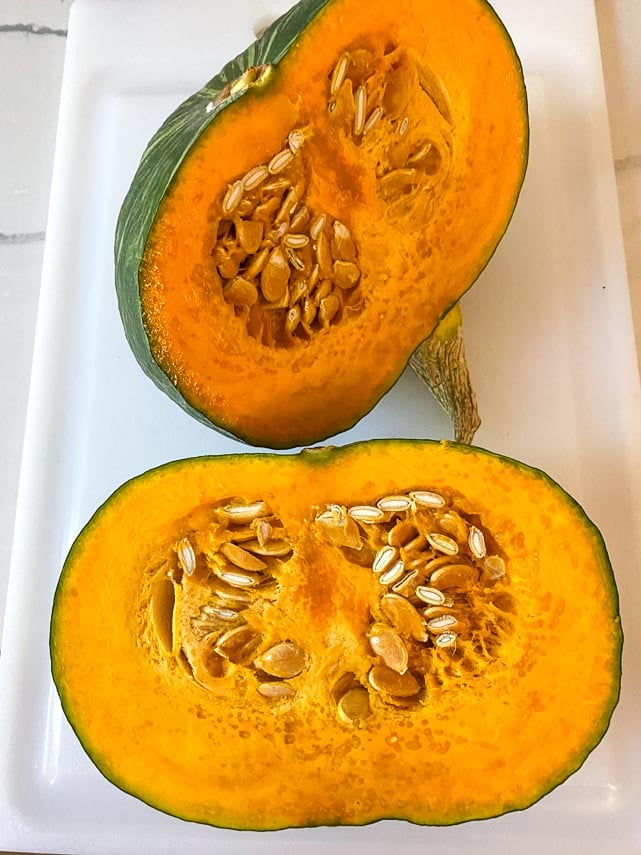 Japanese pumpkin cut in half on white board, showing seeds