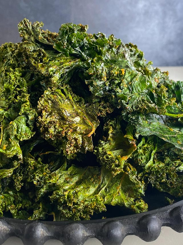 Roasted kale chips piled up on black plate, side view