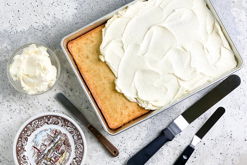 Swiss Meringue Buttercream on yellow cake in pan; icing spatulas alongside