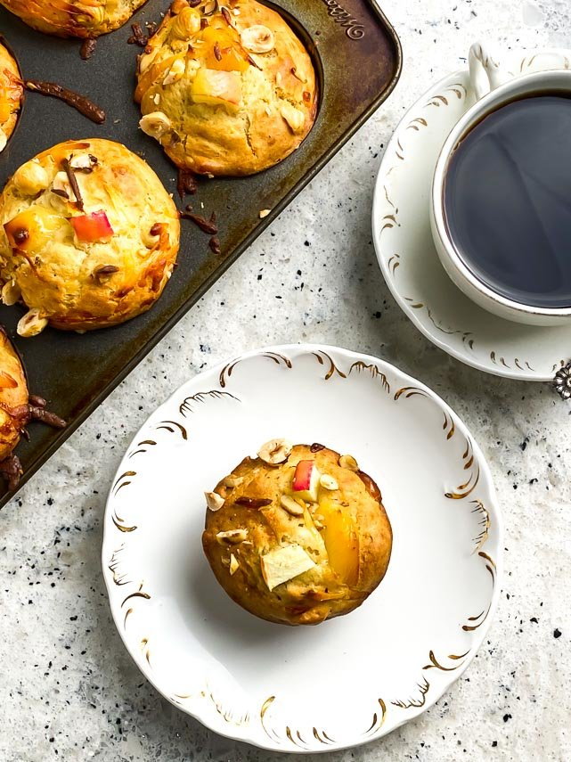 a decorative white plate holding one low FODMAP smoked gouda apple muffin; muffin tin holding muffins and coffee cup in background