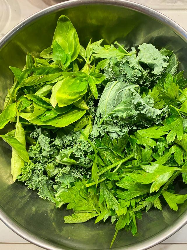 basil, kale and parsley in a stainless steel bowl