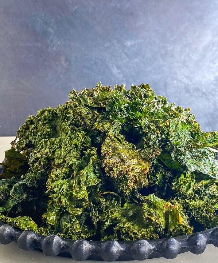 closeup Roasted kale chips piled up on black plate, dark background