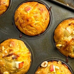 closeup of muffins tins, on the diagonal, holding smoked gouda apple muffins with hazelnuts