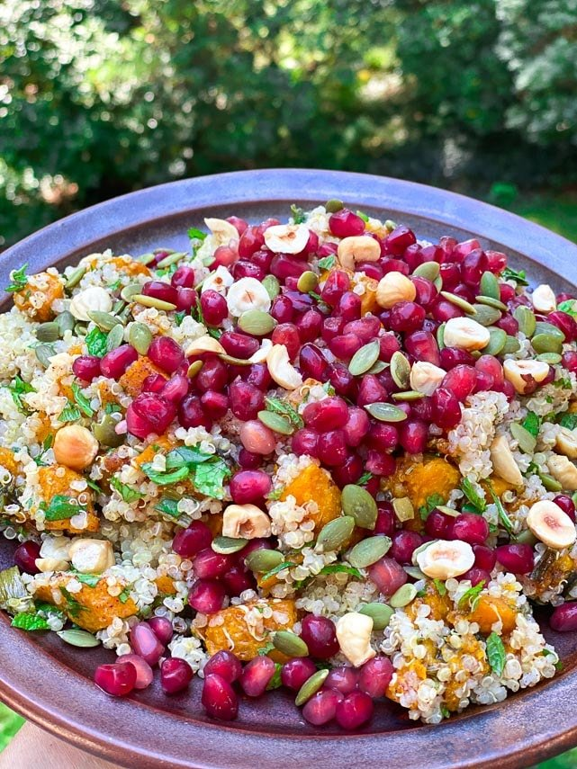 closeup of roasted pumpkin quinoa salad with pomegranate seeds and nuts on brown ceramic plate