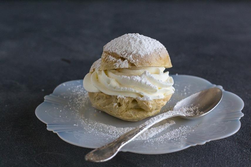 cream puff on white plate with spoon; dark background