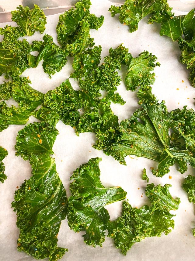 curly kale coated with oil and spices laid out spaced apart on parchment lined sheet pan