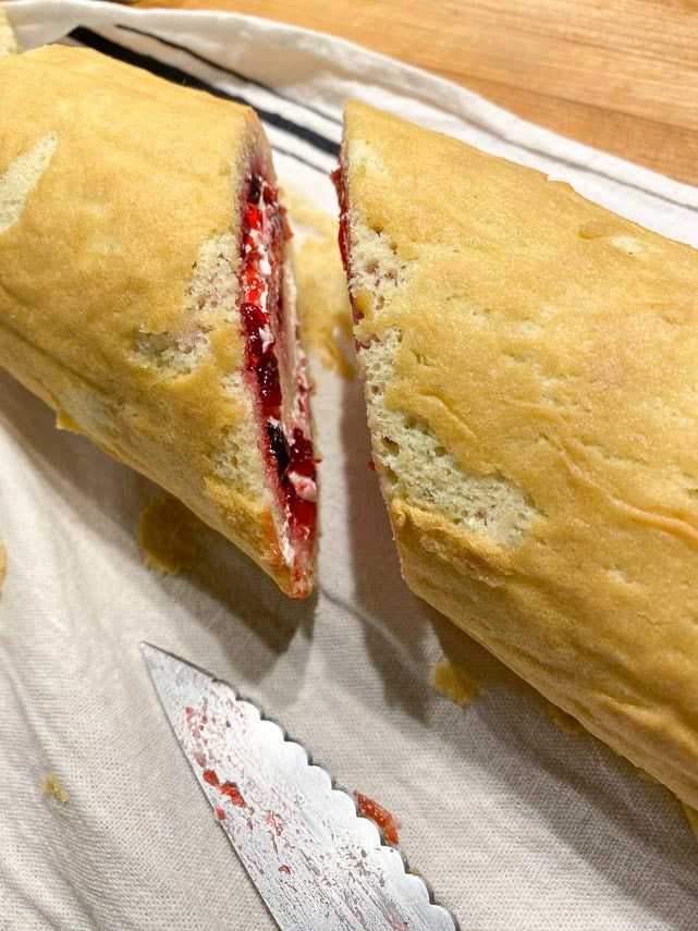 cutting the rolled sponge cake showing cranberry filling