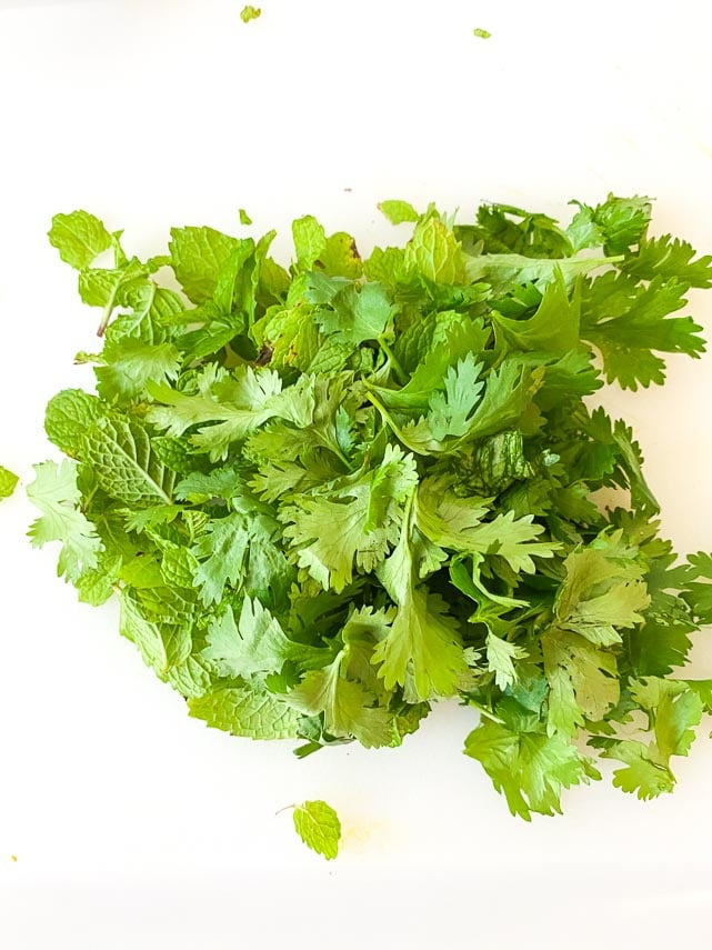 fresh mint and cilantro on white cutting board in a small pile