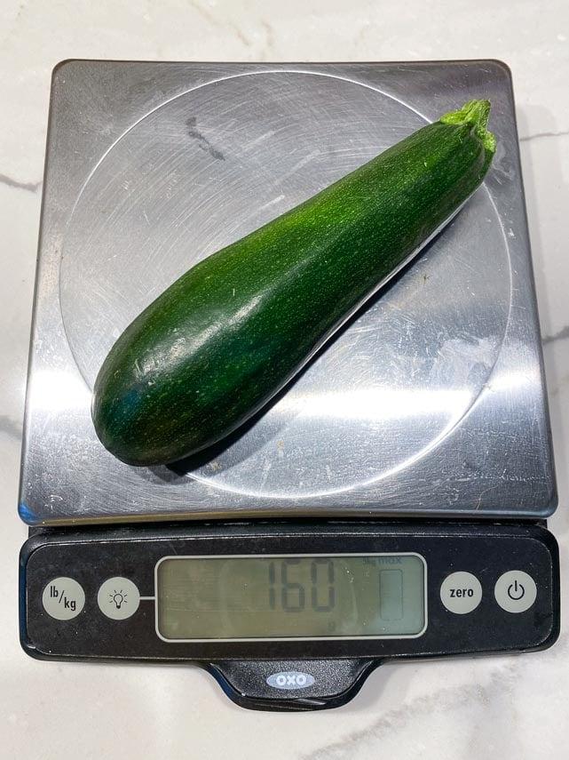 fresh zucchini on scale weighing 160 g