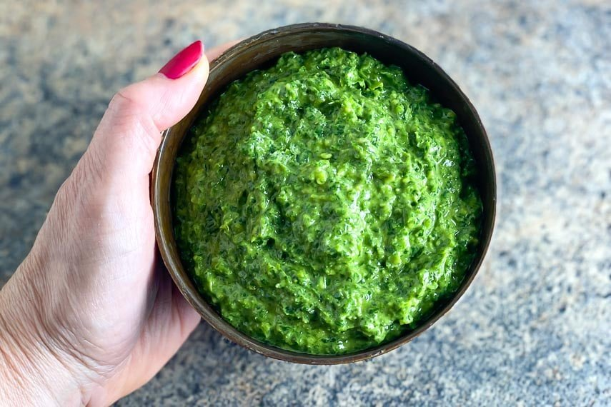 horizontal image of vegan low FODMAP kale pesto in a brown bowl, held by woman's manicured hand over stove surface
