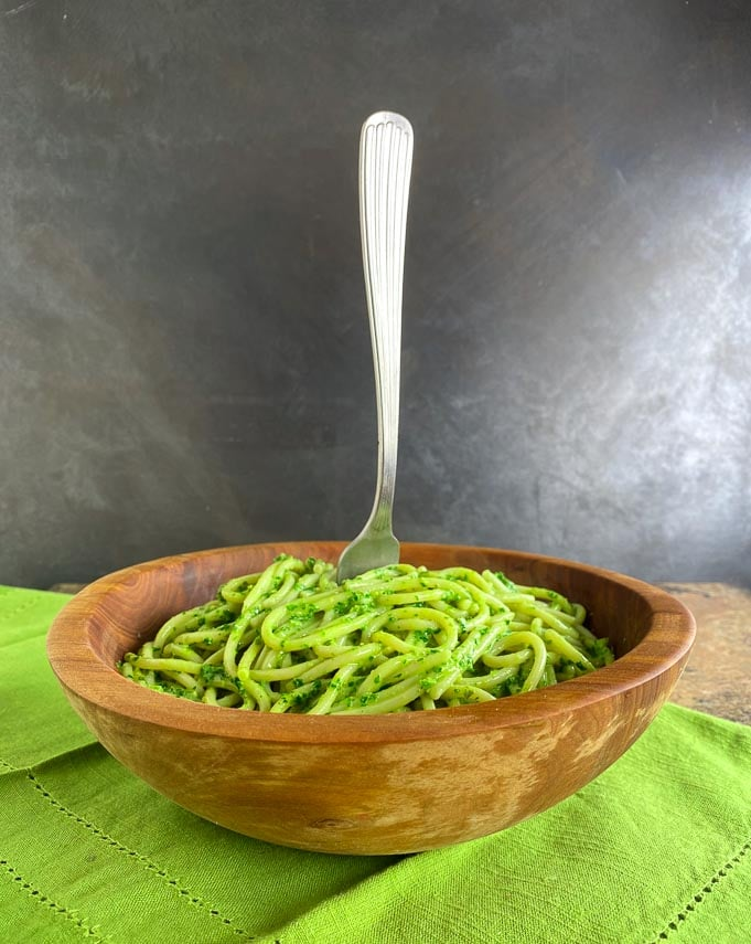 kale pesto on pasta in wooden bowl with fork standing straight up