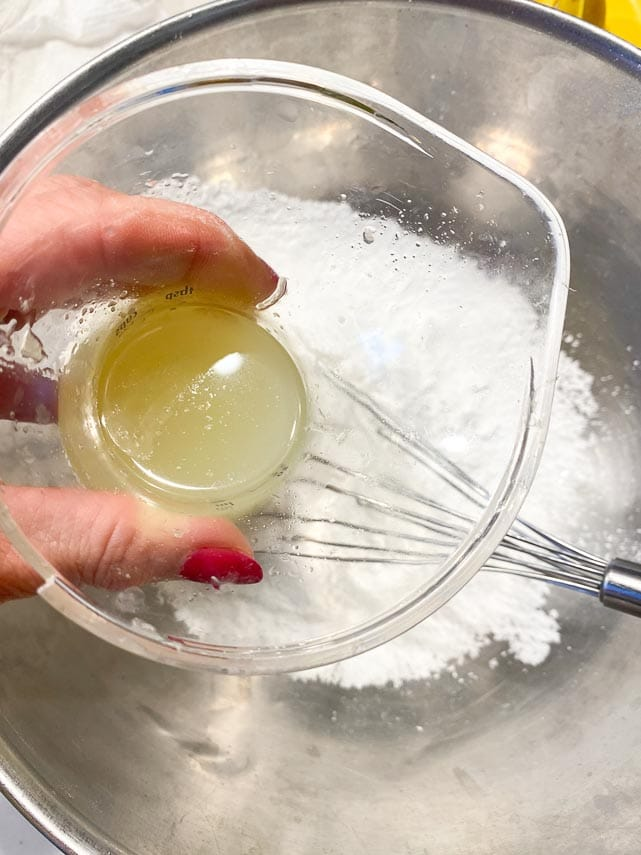 lime juice in small measuring cup with pouring spout hovering over glass bowl of confectioners' sugar