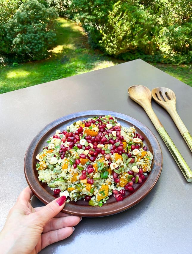 manicured hand with red nails serving a plate of roasted pumpkin and quinoa salad topped with pomegranate seeds and nuts on brown ceramic plate