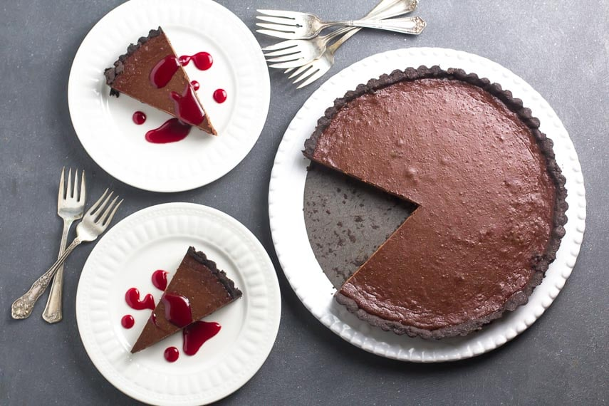 overhead image of low FODMAP Chocolate Caramel Tart; wedges on white plates; whole tart on serving platter; dark background and antique forks