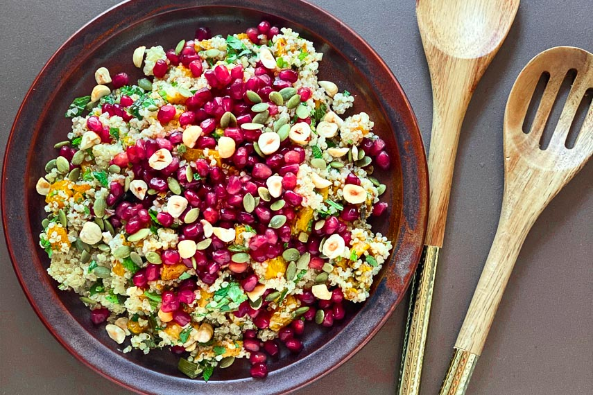 overhead image of low FODMAP Roasted Pumpkin and Quinoa salad with pomegranate seeds and nuts on brown ceramic plate