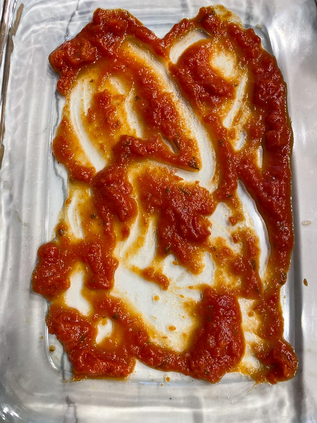 placing a small amount of tomato sauce on bottom of casserole dish so that the zucchini boats don's stick