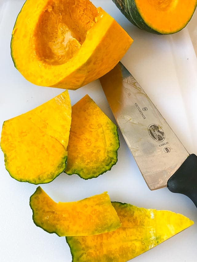 removing green skin with a chef's knife from Japanese Pumpkin, also called kabocha squash, on white board