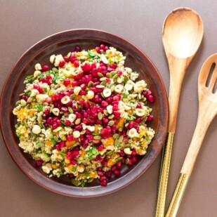 roasted pumpkin and quinoa salad topped with pomegranate seeds and nuts on brown ceramic plate; wooden servers alongside