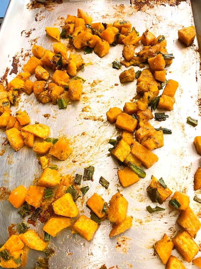 roasted pumpkin cubes and scallion greens on sheet pan