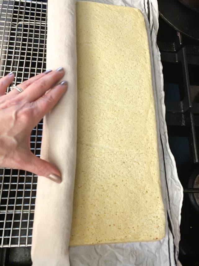 rolling up unmolded sponge cake in linen towel