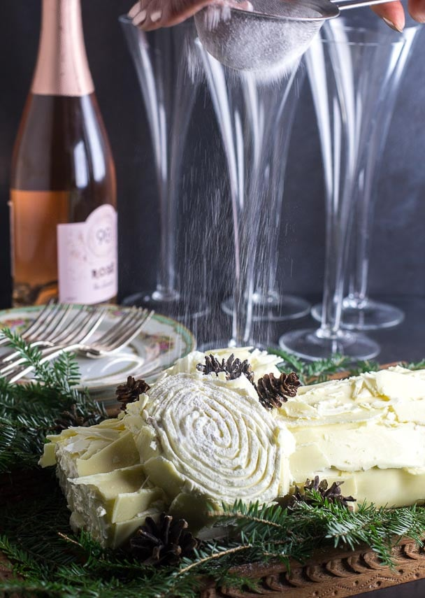 showering confectioners' sugar over a white chocolate buche de Noel on a wooden board; champagne bottle and glasses in background