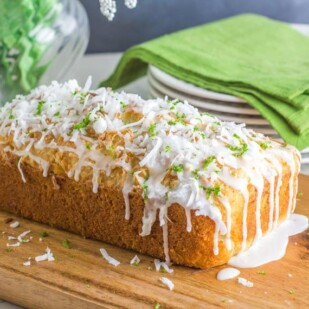 side view of coconut lime bread on a wooden board, icing dripping down; white plates and green napkin in background