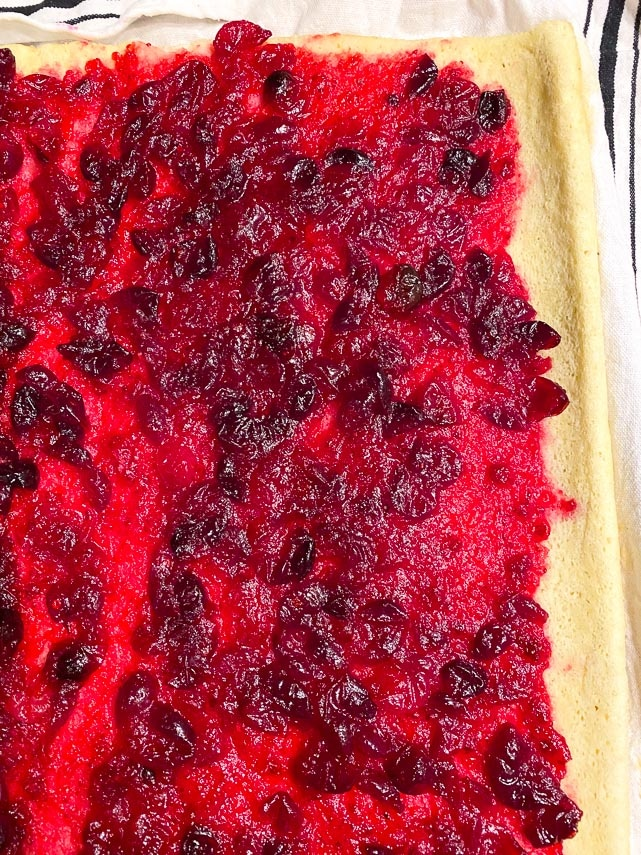 spreading cranberry filling on jellyroll spongecake