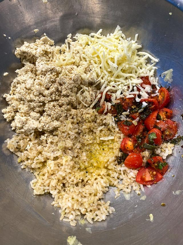 tofu, rice, cheese, tomatoes and egg in metal bowl - the makings of stuffing for zucchini boats