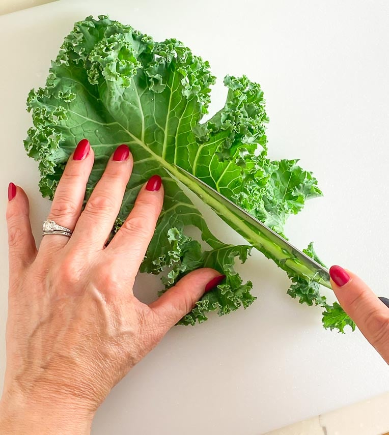 using a knife to remove kale stem
