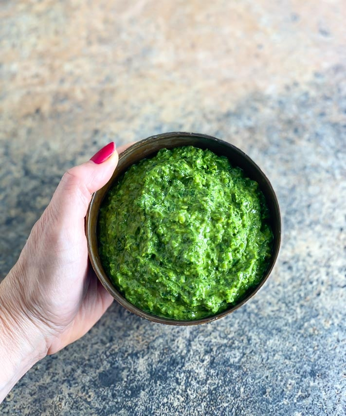 vegan low FODMAP kale pesto in a brown bowl, held by woman's manicured hand over stove surface