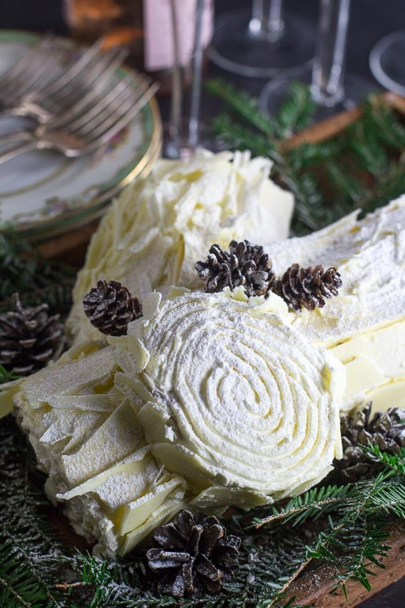 vertical image of a white chocolate buche de Noel with pine boughs and pinecones, dusted with confectioners' sugar