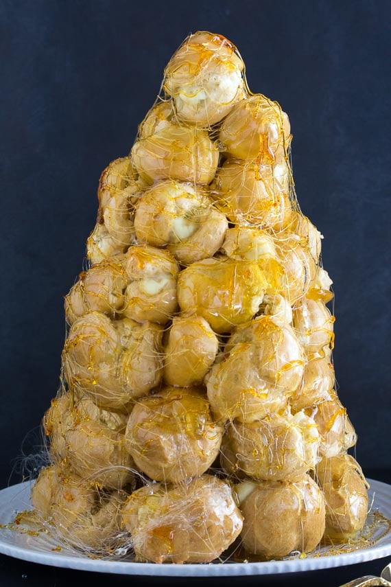 vertical image of croquembouche on white plate against dark background