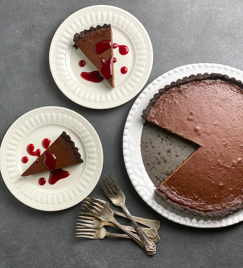 wedges of chocolate tart on white plates with red bloody caramel sauce drizzled all over; whole tart on large white platter and antique forks alongside