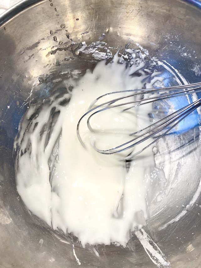 whisking lime juice and confectioners' sugar together in a stainless steel bowl, making a simple glaze