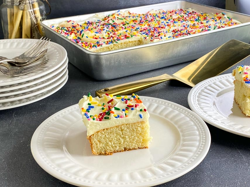 yellow cake square with white frosting and sprinkles on white plate