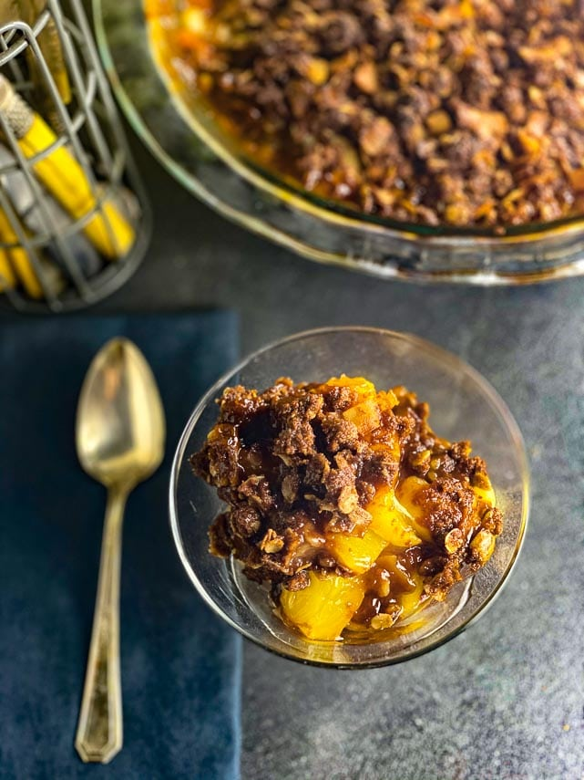Low-FODMAP-Tropical-Crisp-in-a-glass-dish-with-chocolate-crisp-topping-dark-background