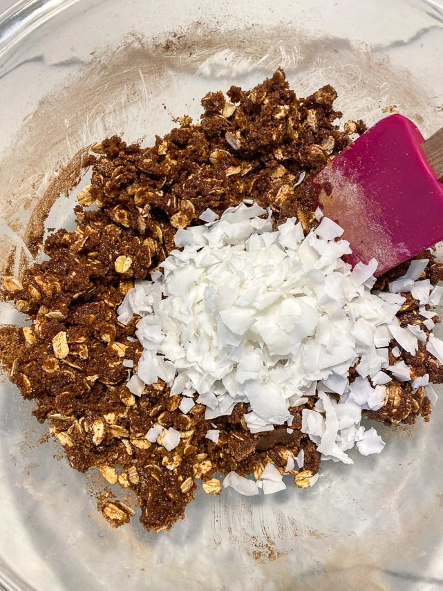 adding-coconut-flakes-to-chocolate-crisp-topping-in-glass-bowl
