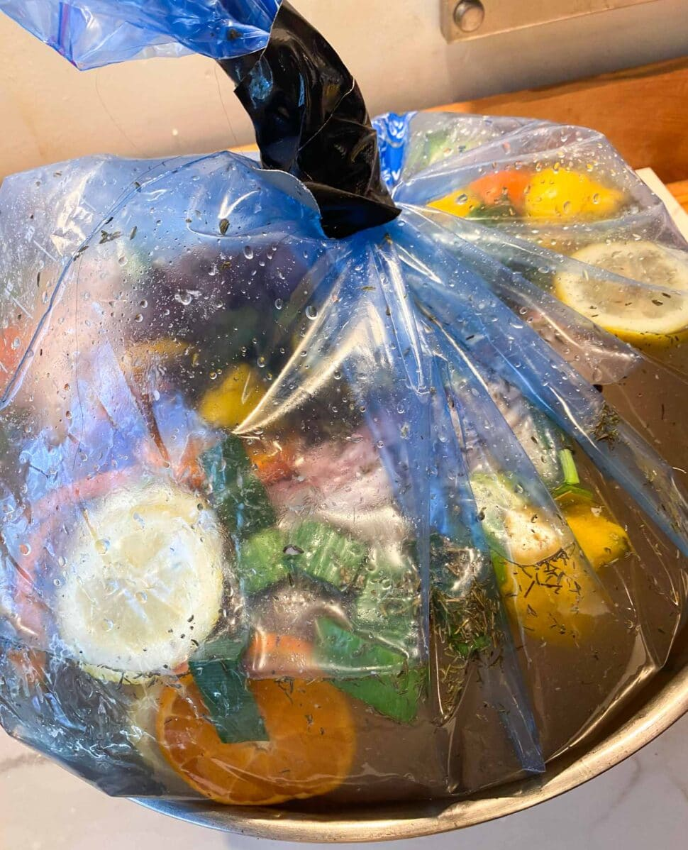 Citrus turkey brining inside a bag, sealed with tape.