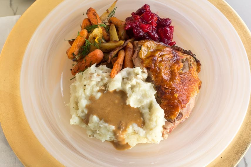 Brined turkey thigh, mashed potatoes, giblet gravy, vegetables and cranberry sauce on a white plate.