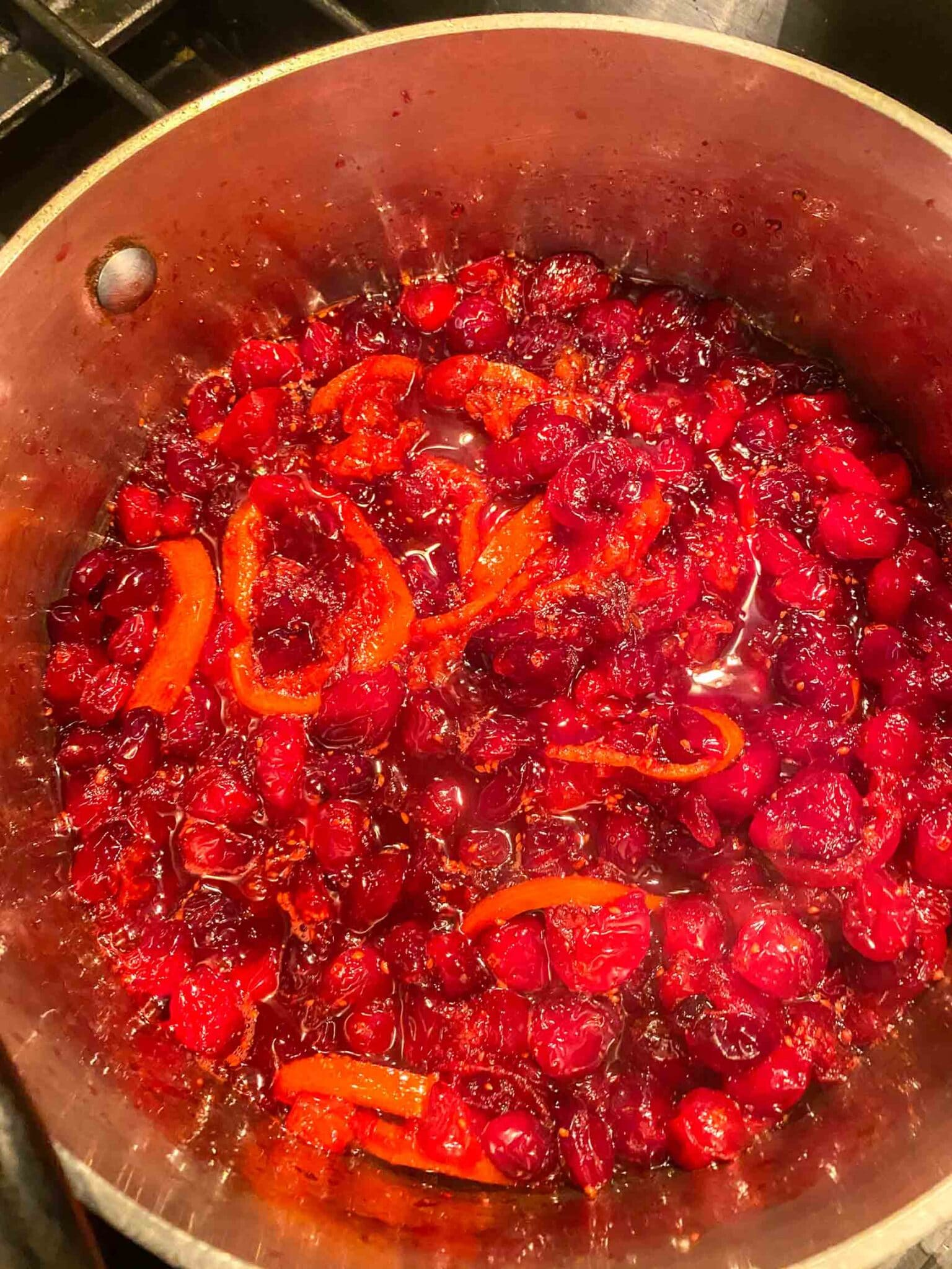 cranberry orange sauce simmering in pot