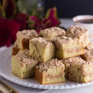 horizontal-image-of-low-FODMAP-one-bowl-streusel-coffee-cake-squares-on-white-plate-coffee-cup-in-background-gold-spatula-in-foreground