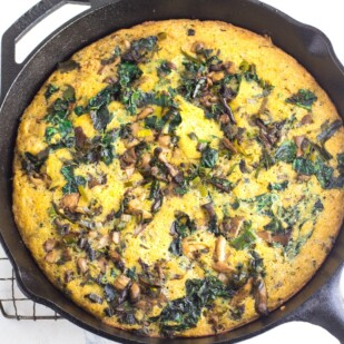mushroom cornbread stuffing in cast iron skillet against white background