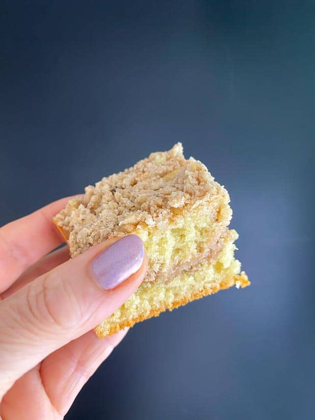 square of coffee cake held in woman's hand in front of blue background