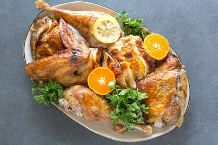 Citrus brined turkey on white oval platter, carved