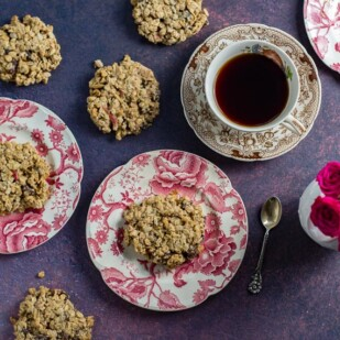 overhead-of-Low-FODMAP-Cinnamon-Apple-Breakfast-Cookies-on-pink-and-white-plates-cup-of-coffee-and-roses-in-background