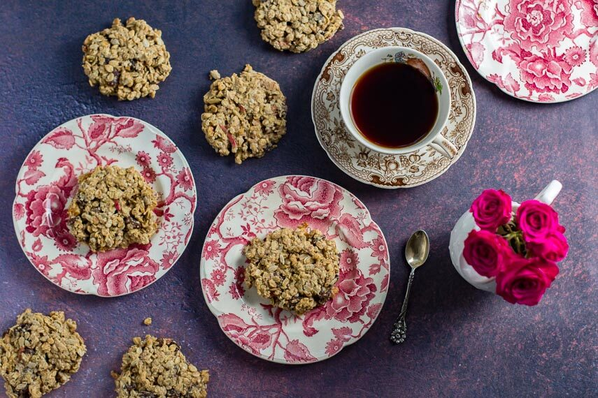 Low FODMAP Apple Oat Breakfast cookies on pink and white decorative plates; coffee and roses alongside