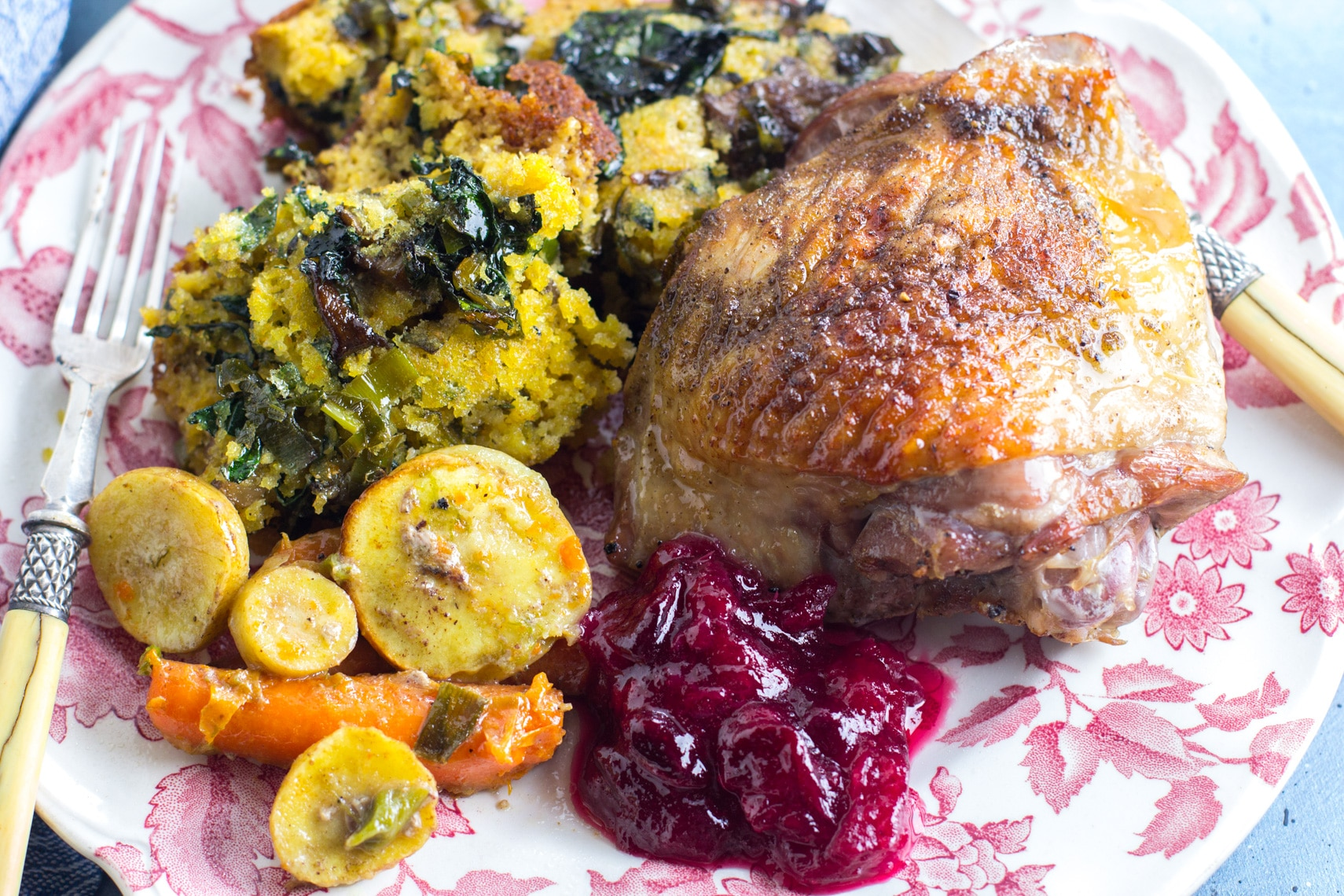 pink and white decorative plate holding stuffing, turkey thigh, cranberry sauce and vegetables; antique fork alongside