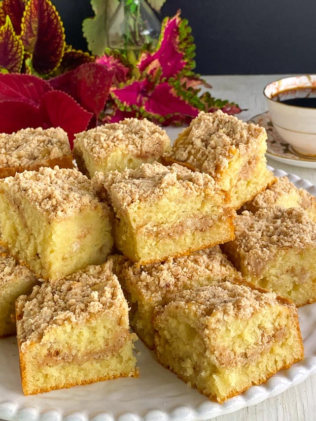 White plate holding squares of low FODMAP one bowl streusel coffee cake; coffee cup in background